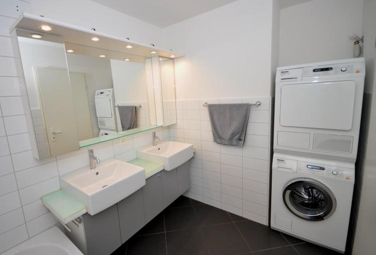 Badezimmer mit Waschmaschine und Tumbler